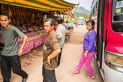09 MARCH 2013 - ALONG HIGHWAY 13, LAOS:  Bus passengers at a rest stop in Hmong hilltribe market on Highway 13 in rural Laos. The paving of Highway 13 from Vientiane to near the Chinese border has changed the way of life in rural Laos. Villagers near Luang Prabang used to have to take unreliable boats that took three hours round trip to get from the homes to the tourist center of Luang Prabang, now they take a 40 minute round trip bus ride. North of Luang Prabang, paving the highway has been an opportunity for China to use Laos as a transshipping point. Chinese merchandise now goes through Laos to Thailand where it's put on Thai trains and taken to the deep water port east of Bangkok. The Chinese have also expanded their economic empire into Laos. Chinese hotels and businesses are common in northern Laos and in some cities, like Oudomxay, are now up to 40% percent. As the roads are paved, more people move away from their traditional homes in the mountains of Laos and crowd the side of the road living off tourists' and truck drivers.    PHOTO BY JACK KURTZ