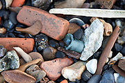A beach glass bottle neck washed up among brick fragments, lumps of coal, and old animal bones on the Thames foreshore, London, UK.