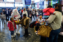 © licensed to London News Pictures. London, UK 17/04/2014. People dressed as Easter bunnies handing out chocolate to children waiting for trains at Euston Station in central London on April 17, 2014 ahead of Easter holiday. Photo credit: Tolga Akmen/LNP