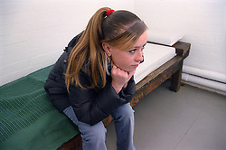 Teenage young offender sitting on bed in police cell,