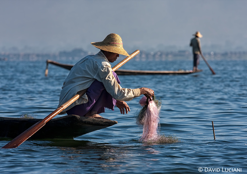 The same man is inspecting his net. In the background you can see another fisher probably looking for a good place.