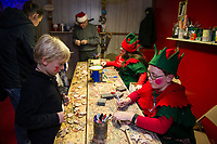 Ray with Santa's elves Lolly and Icy are busy working in Santa's Workshop as Cullyn and Jayda receive an ornament on opening night of the Christmas Village at Laconia's Community Center.  (Karen Bobotas/for the Laconia Daily Sun)