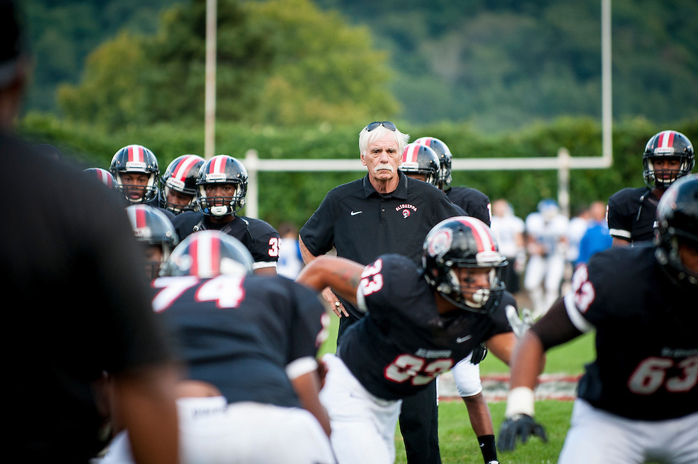 Aliquippa head coach Mike Zmijanac watches over his team during warmups before their homecoming game.<br /> <br /> Zmijanac has never played a down of organized football but he is the winningest coach of what is said to be the best high school program in the region. <br /> <br /> Due to the obstacles of violence and drugs in Aliquippa, Zmijanac says that he loses six or so of his players to the pull of the street each year. And although he will not hesitate to suspend a star player, he maintains an open-door policy if they want to come back, believing that everyone deserves a second chance and that he can't give up on them.<br /> <br /> The school has one of the smallest enrollments in the Western Pennsylvania Interscholastic Athletic League (WPIAL) with the class of 2013 having only 58 kids, including 28 boys.<br /> <br /> Technically, they could play against Class A completion but they elect to play at the AA level.<br /> <br /> Pretty steep obstacles for a coach and team to overcome, but the team averaged 10 wins a year for the past 30 years. Last year Aliquippa played in its 25th WPIAL championship game, the most of any school in the district and they have won a record 15 titles. 2014 was the seventh year in a row that the Quips were in the final, also a record.<br /> <br /> The team was the training ground to NFL greats like Mike Ditka, Sean Gilbert, and Ty Law, all of whom were Aliquippa graduates.