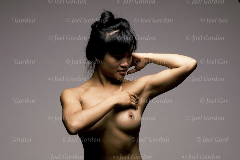 Standing in front of mirror nude Asian American raise one arm to check unusual lumps   Know what is normal for you.  Look and feel.  Become aware of breast changes that may signal a problem.  Report any such changes immediately to your health care professional.<br />