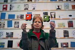 © licensed to London News Pictures. London, UK 23/03/2013. Dee Refaie buys a postcard sized artwork made by Orla Kiely from the Royal College of Art's Secret Postcard Sale. 2,700 postcard sized works of art, which have been donated by artists, designers, illustrators and film-makers including Paula Rego, Julian Opie and David Bailey, sold for £45 at the Royal College of Art in Battersea on Saturday 23 March 2013. Photo credit: Tolga Akmen/LNP