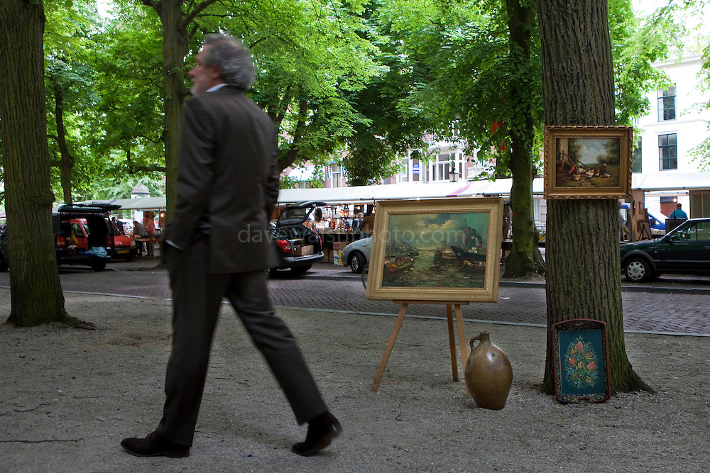 Man walking by artwork for sale, at the Sunday Antique market, The Hague