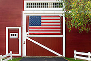 Classic New England farm with red barn and white fence, Vermont USA