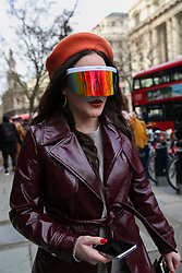 © Licensed to London News Pictures. 14/02/2020. London, UK. A fashion enthusiast wearing coloured fashionable eye shield arrives on day one of the London Fashion Week - Autumn/Winter collection fashion shows in The Strand. Photo credit: Dinendra Haria/LNP