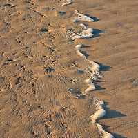 Wave patterns, wind patterns, and the foam from a retreating wave on the winter beach at sunrise, Ocean City Inlet, Ocean City, Maryland