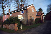 Estate agent's For Sale sign outside semi-detached village house, Shottisham, Suffolk, England