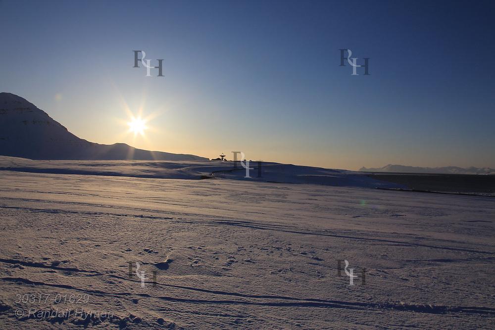 Evening sun skims along horizon in April behind Hamnerabben Airport at the international science village of Ny-Alesund on Spitsbergen island in Kongsfjorden; Svalbard, Norway.