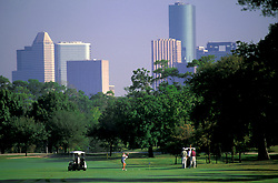 Stock photo of a group golfing with a view of the Houston skyline