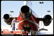 Mechanic closes port on rear of 727 after adding engine oil at Lambert Intl Airport; St. Louis. Missouri