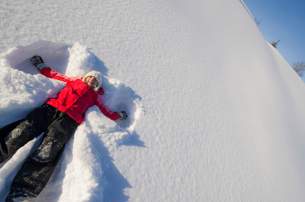 A young girl making a snow angel in deep fresh snow.