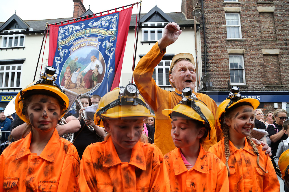 © Licensed to London News Pictures. 09/07/2016. Durham, UK. A former miner dances to the brass bands with four young girls dressed as miners at the Durham Miners' Gala in County Durham, UK. The gala is a large gathering held annually associated with the coal mining heritage and trade unionism. Photo credit : Ian Hinchliffe/LNP