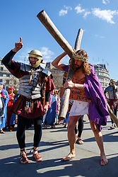 © Licensed to London News Pictures. 25/03/2016. London, UK. Actors of the Wintershall Players perform 'The Passion of Jesus' on Good Friday to crowds in Trafalgar Square on 25 March 2016 in London. The Wintershall Players are based on the Wintershall Estate in Surrey and perform several biblical theatrical productions per year. Their production of 'The Passion of Jesus' includes a cast of 80 actors, horses, a donkey and authentic costumes of Roman soldiers in the 12th Legion of the Roman Army. Photo credit: Tolga Akmen/LNP