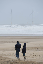 © Licensed to London News Pictures. 23/03/2013..Cleveland, England..A couple walk along a windswept beach at Redcar as the wintery weather continues to chill the country. Cleveland on the east coast of England suffered freezing cold and strong winds that brought big seas to the coastline...Photo credit : Ian Forsyth/LNP
