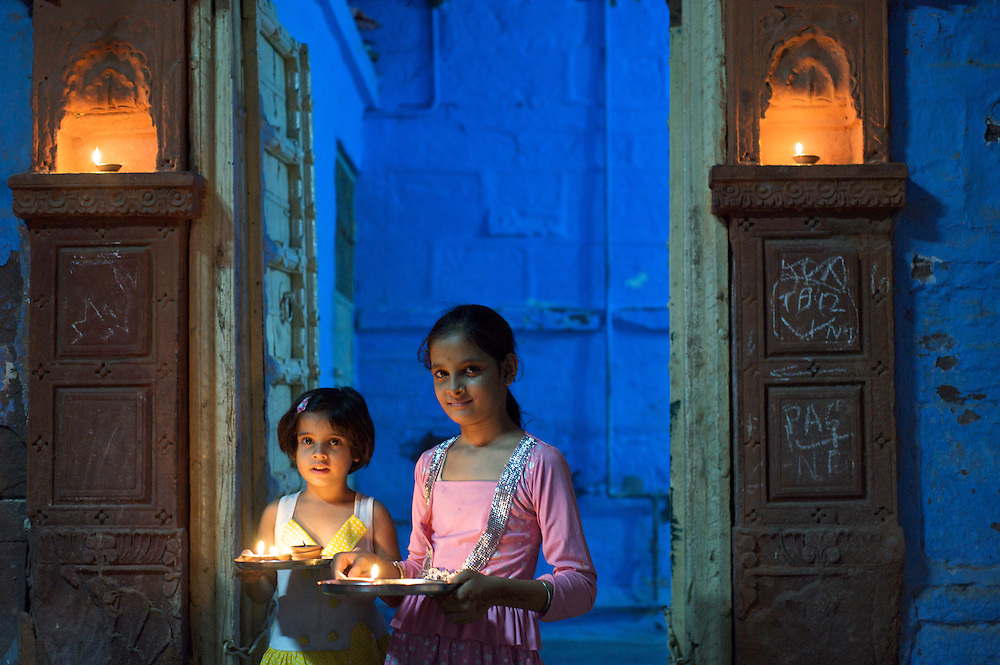 It was Diwali, The Festival of Lights, in Jodhpur and I saw these two girls coming out of their home.  They were carrying sweets to a neighbors house.  I asked them to pause in order to capture that moment for perpetuity.