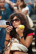 Roma 6 Ottobre 2012.Sabato pomeriggio  sulla scalinata di Trinita dei Monti molte persone consumavano panini e gelati malgrado l'ordinanza del sindaco Gianni Alemanno che vieta il  bivacco e il consumo di panini o bevande.Ragazza mangia una mela e controlla Iphone
