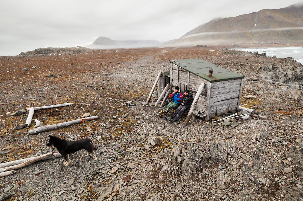 Station cook Dominik Petelski (left) and glaciologist Dariusz Ignatiuk sit together against a historic hut still standing outside the Polish Polar Station in Hornsund, Svalbard. One of the station's huskies stands guard.