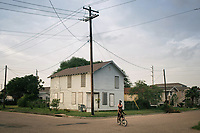 &quot;America in the Middle&quot; is a collection of images showing communities and individuals personally affected by policies but often-overlooked by politicians. |||<br /> <br /> Lauressa Joseph, 14, rides on the back of a bike steered by her brother Gregory Joseph, 13, through their Galveston neighborhood where they live with their mother Freelander Little. Little lost her house during Hurricane Ike in 2008 and now lives in a home elevated eight feet off of the ground. &quot;We came from a broken place to a healed place -- and still striving for better,&quot; Little said.<br /> <br /> Chicago Freelance Photographer | Alyssa Schukar | Photojournalist