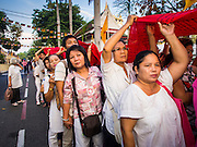 30 OCTOBER 2014 - BANGKOK, THAILAND: People carry the red cloth that will be placed around the chedi at Wat Saket during the parade marking the start of the temple's annual fair. Wat Saket is on a man-made hill in the historic section of Bangkok. The temple has golden spire that is 260 feet high which was the highest point in Bangkok for more than 100 years. The temple construction began in the 1800s in the reign of King Rama III and was completed in the reign of King Rama IV. The annual temple fair is held on the 12th lunar month, for nine days around the November full moon. During the fair a red cloth (reminiscent of a monk's robe) is placed around the Golden Mount while the temple grounds hosts Thai traditional theatre, food stalls and traditional shows.   PHOTO BY JACK KURTZ