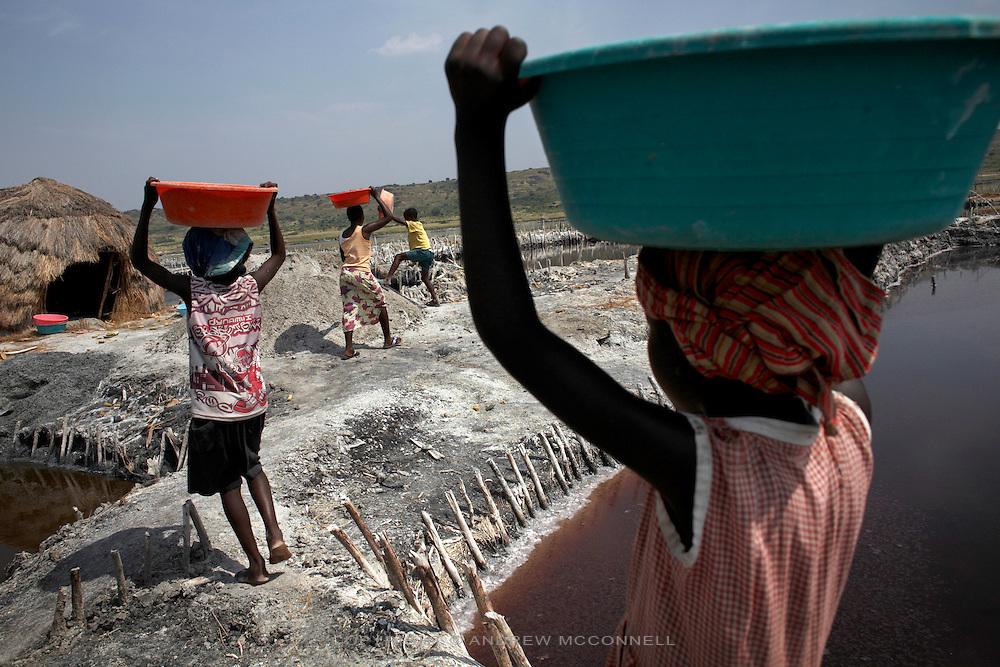 Children carry basins of salt at Lake Katwe.