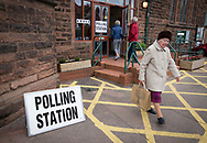 Voters arriving at and leaving a polling station in West Kirby, Wirral to cast their votes at the 2015 UK General Election. They were voting in the marginal Wirral West constituency, held since the 2010 election by Esther McVey MP for the Conservative Party. Voters went to the polls across the UK on 7th May to elect 659 member of parliament.