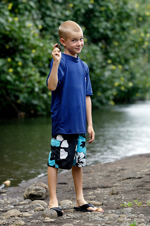 A young boy stops to skip rocks while kayaking the Hanalei River with his family en route to the Hanalei National Wildlife Refuge on the North Shore of Kauai.