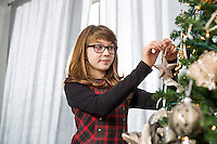 Teenage girl hanging ornament on Christmas tree at home
