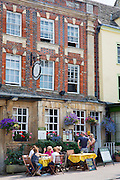 Diners at The Bull medieval inn traditional old gastro pub hotel in Burford High Street in The Cotswolds, Oxfordshire, UK