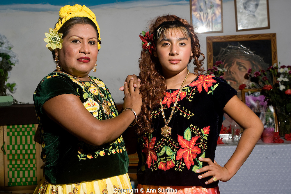Juchitan, Mexico: Jesusa Hernandez (yellow) and her nephew Julio Valdiviezo Hernandez (red) are muxe, or transvestites, in the Oaxacan town of Juchitan, on Sept. 13, 2008. Here they pose in Jesusa's home, in traditional Tejuana clothing. Muxes are very common, and accepted, in this Southern Oaxacan region, which claims to not discriminate against gays. The matriarchal society is still driven by women but in flux in the machismo culture of Mexico. (photo: Ann Summa).