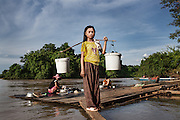 "A young girl heads back home after filling buckets with river water for daily use. Despite hosting only 12 families, the village of Phluk, located 11 km downstream the dam's construction site, was once famous for his fishing community. Local fishermen used to earn between $15 and $25 per day selling fish to the surrounding communities. Now because of the dam and the calcium carbide they use for drilling, the amount of fish in the area has dropped dramatically. ""The village is now very quite and we no longer sell fish since there's barely enough to feed ourselves. We only have buffaloes and chickens but with the deforestation going on around here it's getting harder and harder. As if this wasn't enough, the rain stopped too. We are cursed"" - Bun Aeng, 50, fisherman."
