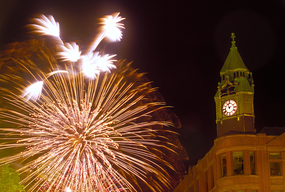 Fourth of July fireworks burst behind the historic Savings Bank building in Marquette, Mich.
