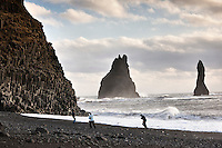 Reynisfjara black sand beach, south shore Iceland. Sea stacks in background. People running from the wave.