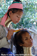 A Karen Paduang refugee from Burma (Myanmar) combs her mother's hair in Ban Nai Soi, Thailand.  The Karen people left Burma to flee war atrocities and are considered a tourist attraction by the Thailand government.