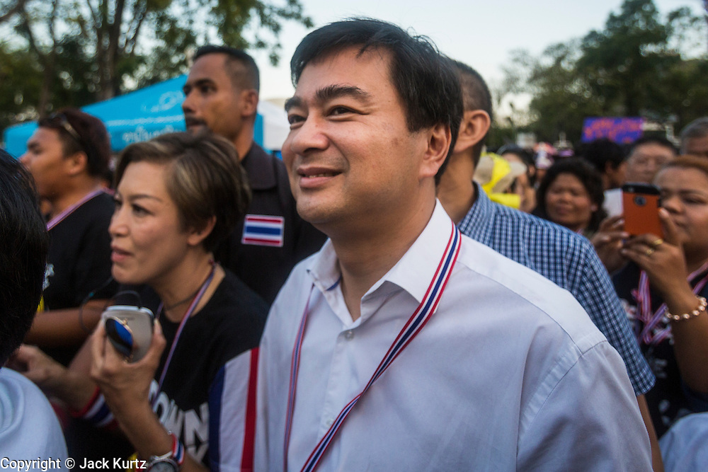 """13 JANUARY 2014 - BANGKOK, THAILAND: Former Thai Prime Minister ABHISIT VEJJAJIVA, a leader of the Democrat party, walks through the anti-government protest in Lumpini Park. Abhisit and all of the other Democrats, the opposition party in Thailand, resigned from Parliament and are not participating in the coming election. Tens of thousands of Thai anti-government protestors took to the streets of Bangkok Monday to shut down the Thai capitol. The protest was called """"Shutdown Bangkok"""" and is expected to last at least a week. The Shutdown Bangkok protest is a continuation of protests that started in early November. There have been shootings almost every night at different protests sites around Bangkok, including two Sunday night, but the protests Monday were peaceful. The malls in Bangkok stayed open Monday but many other businesses closed for the day and mass transit was swamped with both protestors and people who had to use mass transit because the roads were blocked.    PHOTO BY JACK KURTZ"""