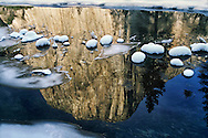 Reflections in the Merced River of the 3000' foot granite monolith, El Capitan, in Yosemite National Park punctuated by snow capped rocks offer a vison of peace and solitude away from the hurry-up world of the holiday season.  Jay Mather photo, 12-18-94