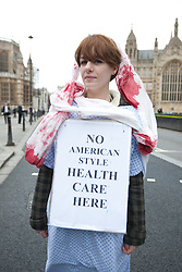 © licensed to London News Pictures. London, UK 27/02/2012. A NHS protester is pictured as protesters are blocking Arbingdon Street, next to the Houses of the Parliament as they protest the government's NHS reform. Photo credit: Tolga Akmen/LNP