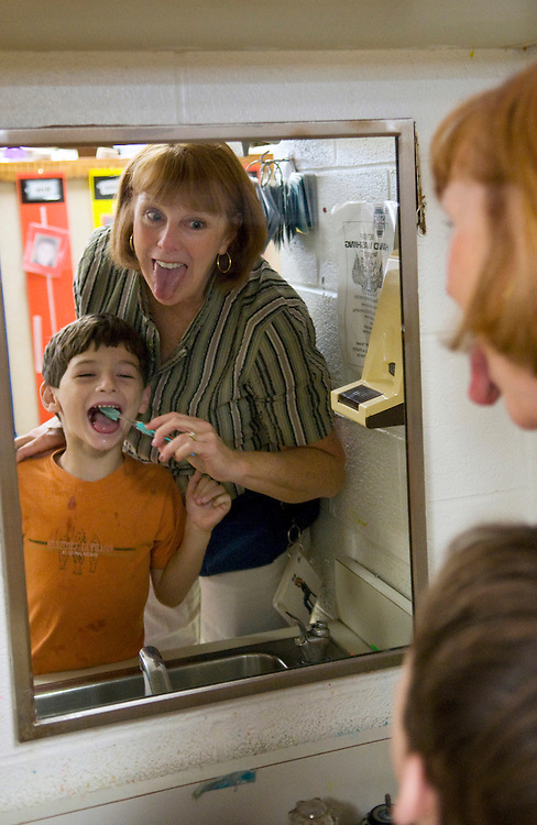Lissa Riley helps Jared West, 5, brush his teeth after eating breakfast..