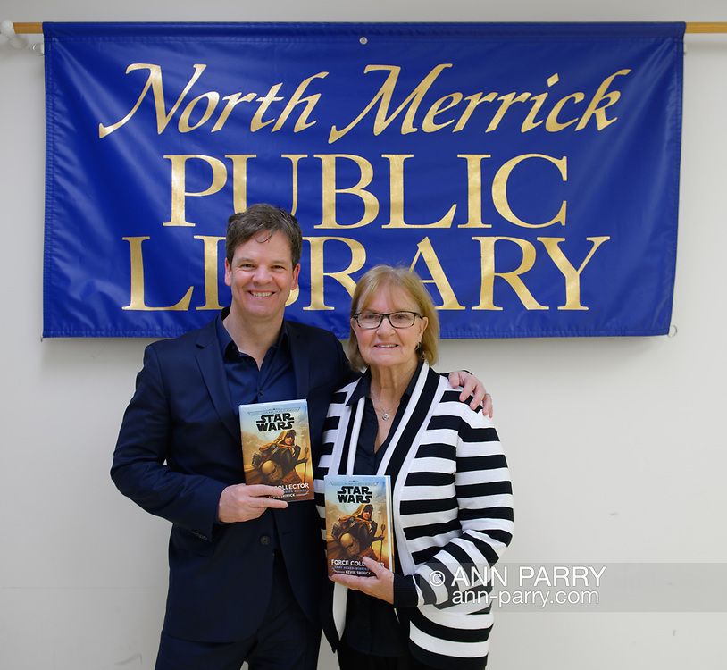 Merrick, New York, U.S.  December 20, 2019.  L-R,  Author KEVIN SHINICK and his mother LOUISE SHINICK, both holding his novel, pose at North Merrick Public Library banner during book signing for his STAR WARS: FORCE COLLECTOR, on Nassau County Force Collector Day. Kevin Shinick named home planet of Karr Nuq Sin, the main character of this official canon Star Wars young adult novel, MEROKIA in honor of Merokee tribe who settled his Merrick hometown on Long Island.