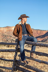 hot cowboy sitting on a rustic fence