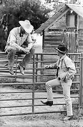 two cowboys by a fence on a ranch