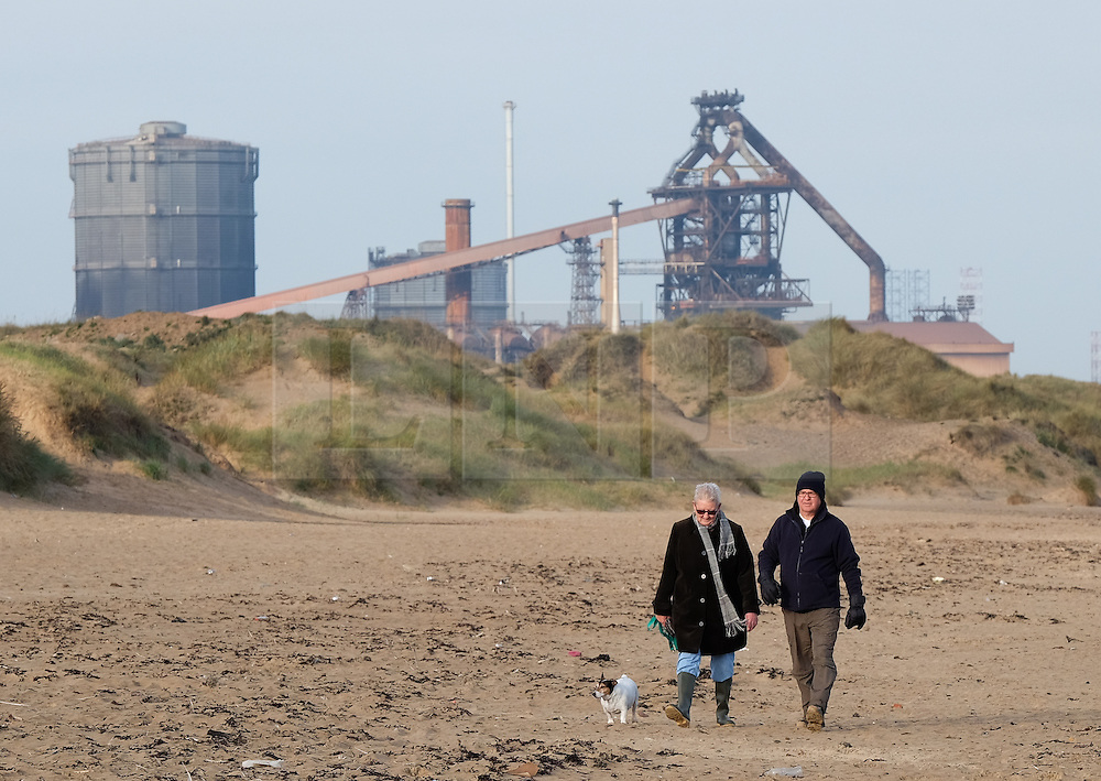 © Licensed to London News Pictures.20/10/15<br /> Redcar, UK. <br /> <br /> A couple walk their dog on the beach in front of the recently closed SSI UK steel blast furnace in Redcar, England. The closure of the site marks the end of 170 years of steel making heritage on Teesside and was the first of a number of recent closures of steel making plants across the UK.<br /> <br /> Photo credit : Ian Forsyth/LNP