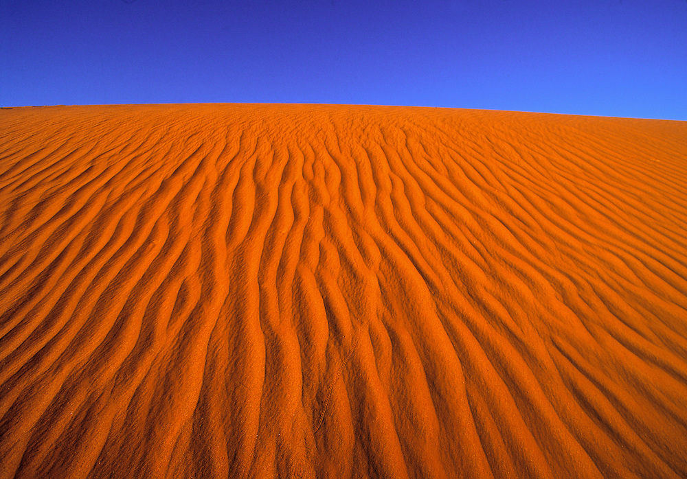 The wind ripples in the sand dune seem to flow uphill to the sky in Monument Valley, Utah.