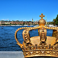 Gilded Crown on Skeppsholm Bridge in Stockholm, Sweden<br /> This gilded crown sits on the railing of a wrought iron bridge called Skeppsholmsbron.  Built in 1861, the Skeppsholm Bridge connects the Blasieholmen peninsula with the Skeppsholmen islet.  Once a naval base, the island has been transformed into parks and a cultural center for museums.  In the background is the channel called Ladug&aring;rds-landsviken and the buildings along Stranv&aring;gen Boulevard.