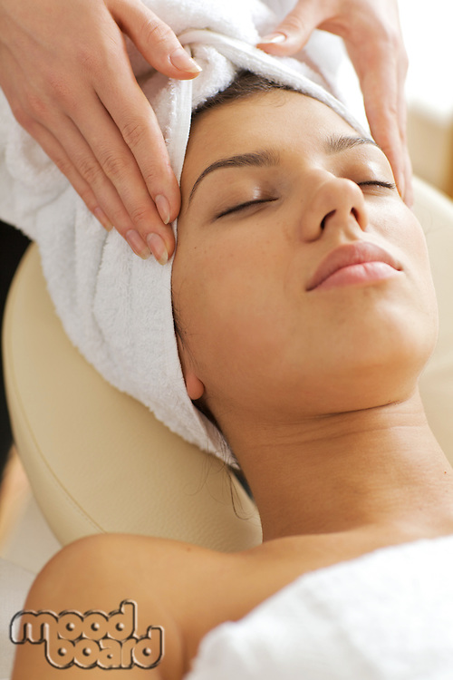 Young woman receiving energy therapy, eyes closed