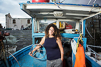 """POZZUOLI, ITALY - 8 OCTOBER 2016: Cristina Pinto (47), also known as """"Nikita"""", a former Camorra killer turned into a fisherwoman, poses for a portrait by her fishing boat in the port of Pozzuoli, a city of the Metropolitan area of Naples, Italy, on October 8th 2016.<br /> <br /> Cristina Pinto started her criminal career at 16 with armed robberies. By the time she turned 20 years old, she became the bodyguard of Camorra boss Mario Perrella as well as the first woman to become a killer for the criminal organization. When she was arrested in 1992, at the age of 22 years old, she was charged and sentenced for at least three homicides and for criminal conspiracy. She spent the following 22 years in prison. When released, she became a fisherwoman. She now fishes with her partner Raffaele."""