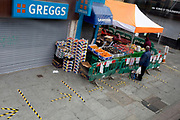 "The UK Chancellor Rishi Sunak has said it is ""very likely"" the UK is in a ""significant recession"" due to the Coronavirus pandemic lockdown, as figures show the economy contracting at the fastest pace since the financial crisis. And in the face of continued lockdown on the high street such as here on the Walworth Road in south London, a lone shopper buys essential fruit and veg at East Street market where customers must observe social distancing with marks on the pavement on 13th May 2020, in London, England."
