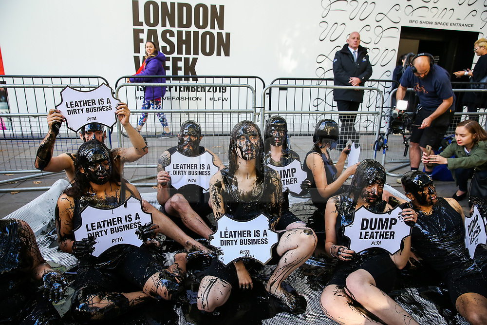 """© Licensed to London News Pictures. 13/09/2019. London, UK. The campaigners from People for the Ethical Treatment of Animals (PETA) protests against the hazardous waste associated with the leather industry are covered in black """"toxic slime"""" on the opening day of London Fashion Week. Photo credit: Dinendra Haria/LNP"""